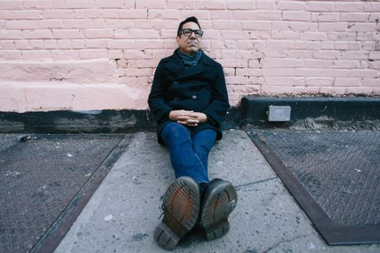 Charles Sanchez sits on a sidewalk in New York City