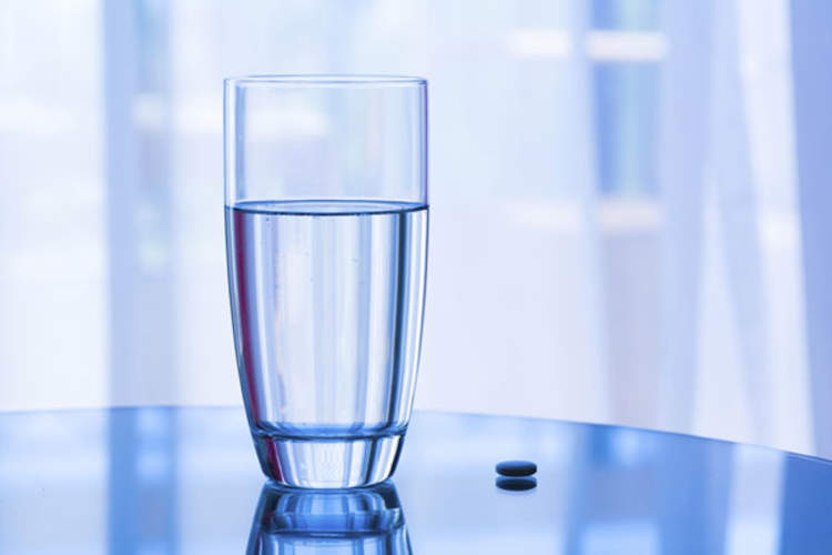 glass of water and pill sitting on table