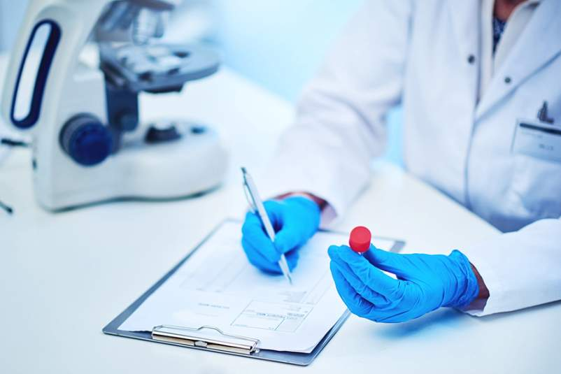 Medical researcher holding a blood sample and writing on a clipboard