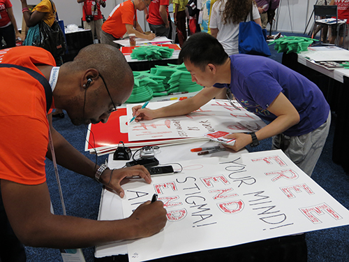 Harlan Smith, of Atlanta, Ga., and Tony Zheng, of China, make signs before the mobilization begins.