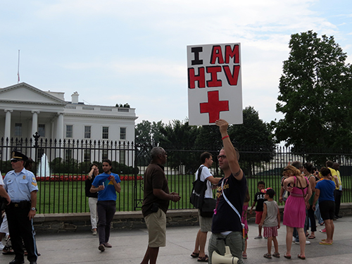 A protestor mingles with tourists on the sidewalk in front of the White House.