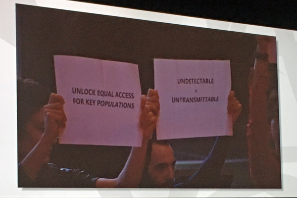 Activists at the IAS 2017 opening session hold up signs saying, 'Unlock equal access for key populations' and 'Undetectable = Untransmittable' (Credit: Warren Tong)