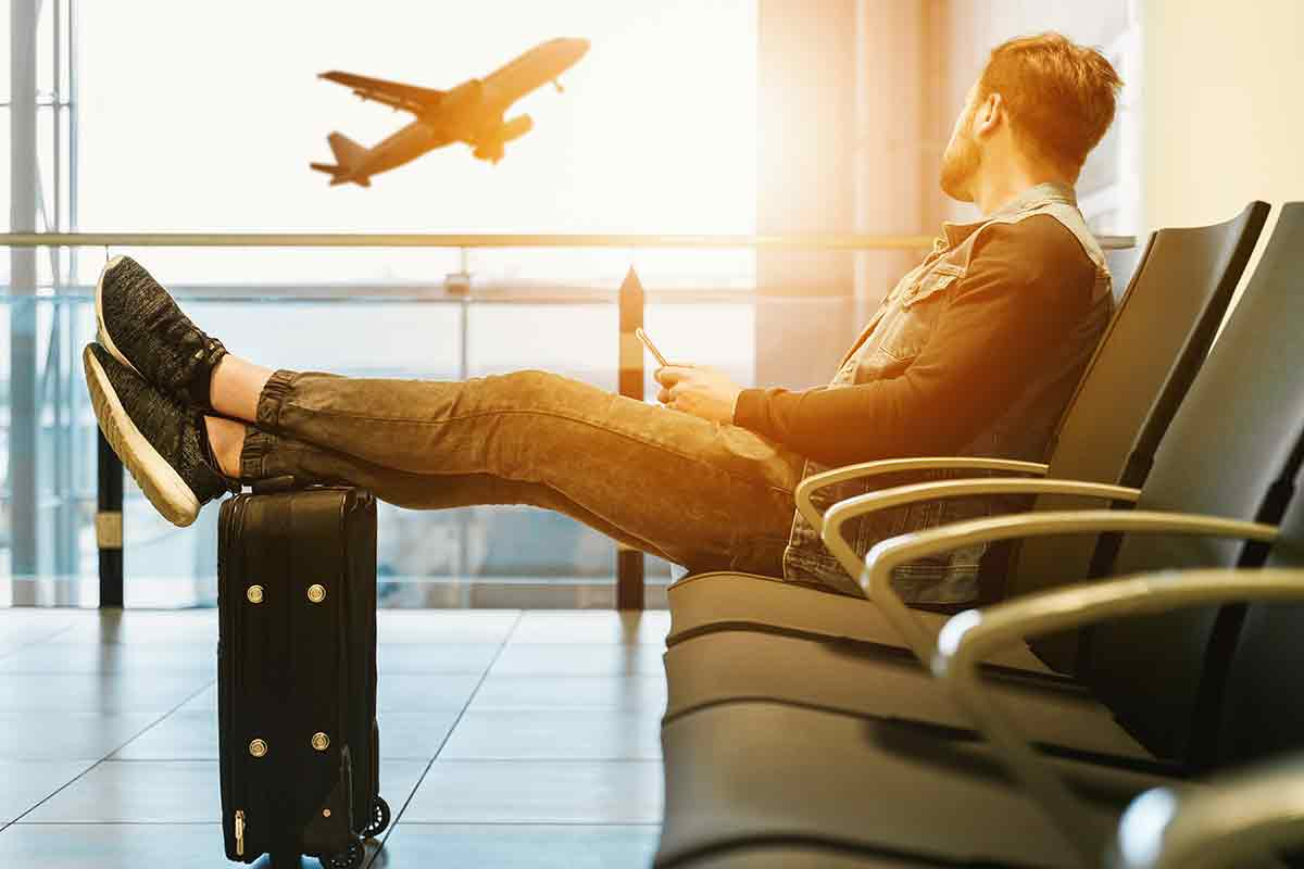 Young business owner watches an airplane take flight while waiting for his flight