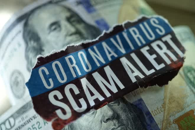 "This is a photo of $100 bills. In the middle of the photo the words ""coronavirus scam alert"" are written."