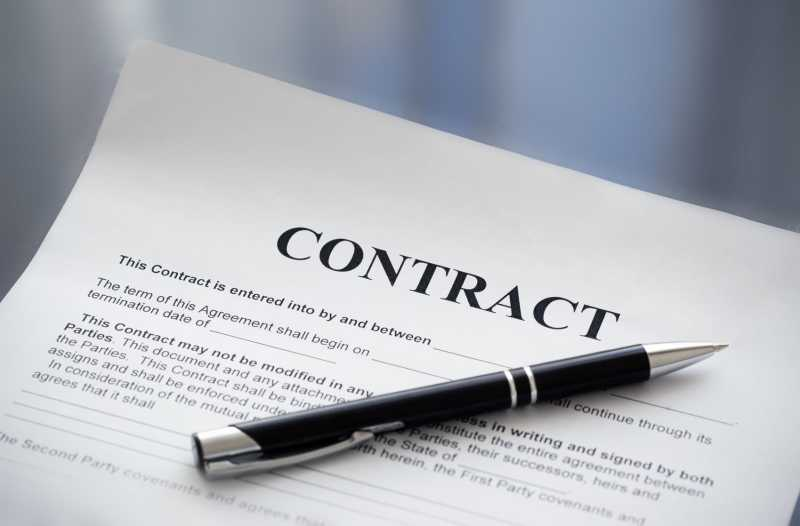 This is a photo of a sample contract. The photo also includes a black pen.