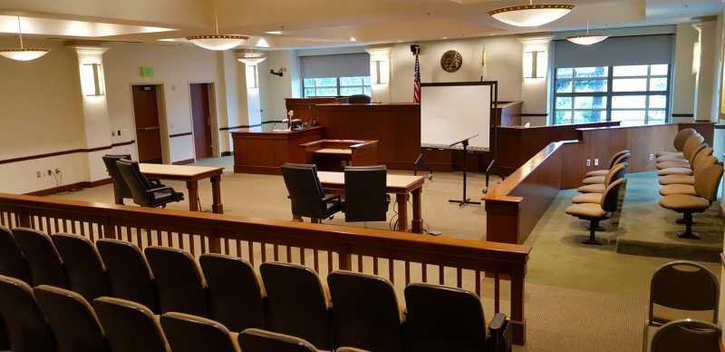 This is a photo of inside a courtroom. The photo shows the jury box to the right; counsel tables; judges bench; witness box; clerks box and the gallery. It also includes a screen.