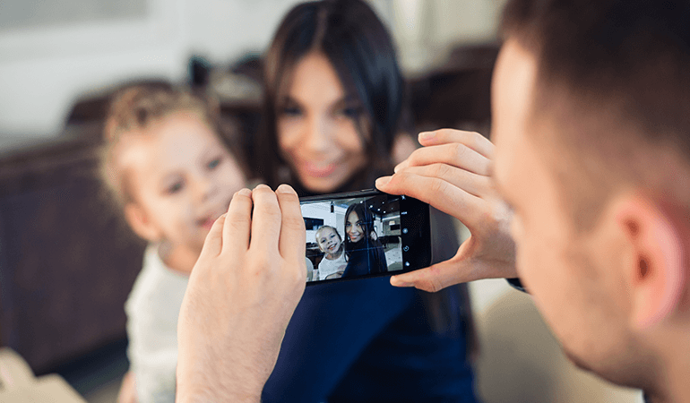 Father taking picture of two kids on smartphone