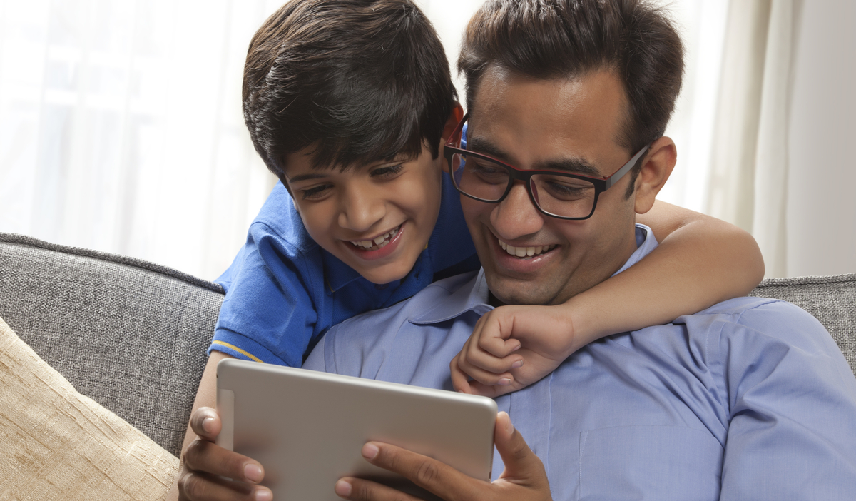 happy father and son holding tablet