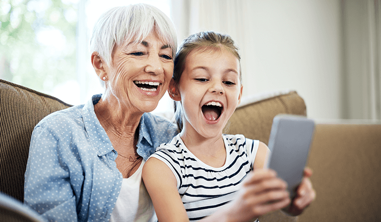 Happy grandmother and grand daughter using a smartphone