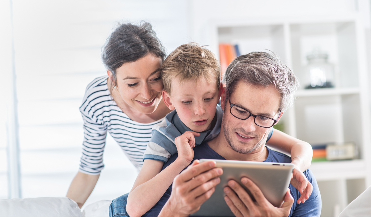 Mom, dad, and son playing game on a tablet