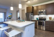 Kitchen with stainless steel appliances and island with space for bar stool seating