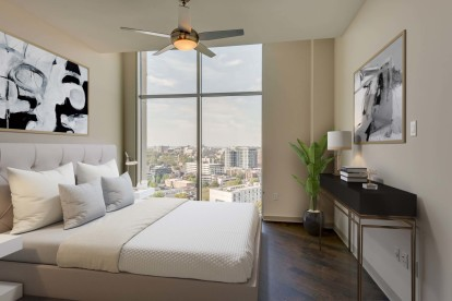 Camden Music Row Apartments Penthouse bedroom with floor-to-ceiling windows and hardwood-style flooring