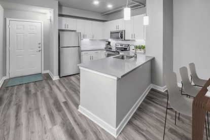 Contemporary midrise apartment kitchen with granite countertops and pendant lighting