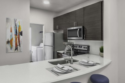Townhome floor plan kitchen alongside laundry room with full size washer and dryer and shelving