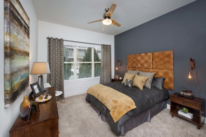 Black granite finishes bedroom with carpet and ceiling fan