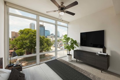 Bedroom with floor to ceiling windows ceiling fan and carpet flooring