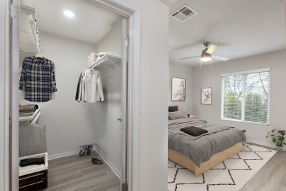 Bedroom with walk in closet wood look flooring and ceiling fan