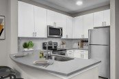 Kitchen with quartz countertops stainless steel appliances undermount sink and glass cooktop