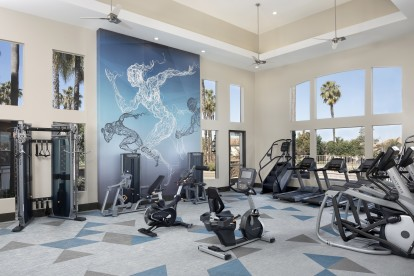 Fitness center cardio equipment with windows and a ceiling fan