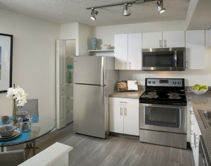Eat in kitchen with stainless steel appliances track lighting wood look flooring and pantry