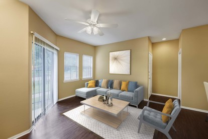 Living room with sliding glass doors to patio ceiling fan and wood look flooring