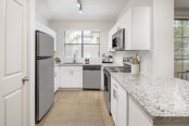 Kitchen with stainless steel appliances, quartz countertops, and white cabinetry