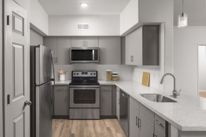 Spacious kitchen with stainless steel appliances, white quartz countertops, white subway tile backsplash, brushed nickel fixtures, and wood-like flooring