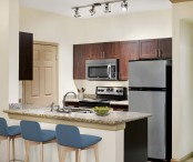 Kitchen with granite countertops stainless steel appliances and track lighting