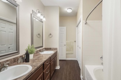 Bathroom with wood style flooring double sinks and curved shower rod
