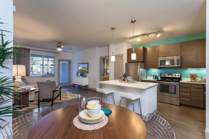 Open concept dining area near kitchen island with stainless steel appliances