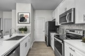 Kitchen with stainless steel appliances and gray subway backsplash