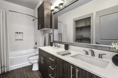 Bathroom with double sink and curved shower rod
