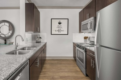 Kitchen with granite countertops, hardwood-style flooring, and dark wood cabinets.