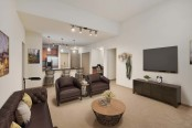 Open concept living with high ceilings track lighting and carpet flooring