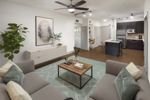Open concept living and kitchen with track lighting ceiling fan and wood look flooring