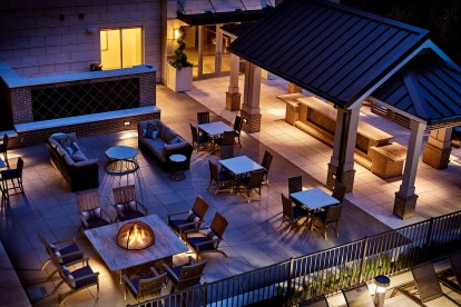 Outdoor lounge with fire pits and grills nighttime view