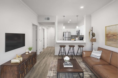 Open-concept living and dining room near contemporary kitchen with white quartz countertops, gray subway tile backsplash, and stainless steel appliances