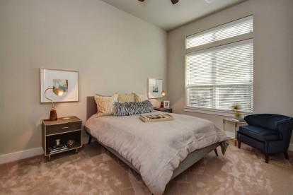 The townhomes bedroom with high ceilings ceiling fan and carpet flooring
