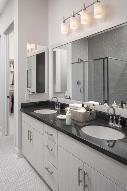 Penthouse bathroom with dual vanity sinks glass enclosed shower and walk in closet