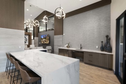 Resident club demo kitchen with barstool seating and quartz countertops
