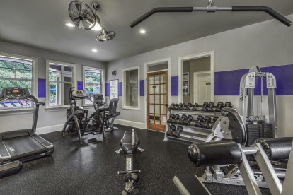 24 hour fitness center with cardio and strength training equipment including free weights