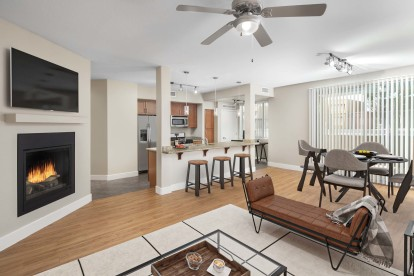 Open concept living room with fireplace and dining room near kitchen island with barstool seating