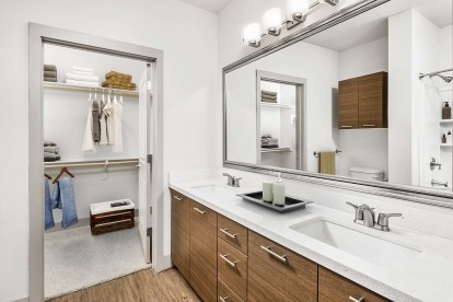 Bathroom with dual vanity sinks walk in closet and framed mirrors
