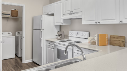 Kitchen with laminate countertops and white appliances next to laundry room at Camden Governors Village Apartments in Chapel Hill, NC