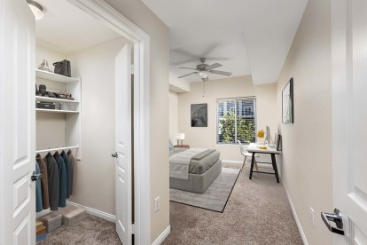 Traditional style bedroom with walk in closet and ceiling fan and space for a desk