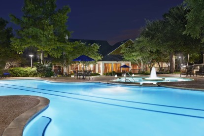 View of resort style swimming pool with lap lanes at night