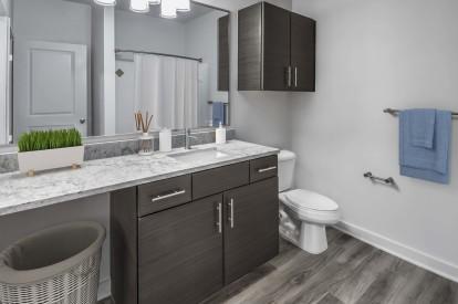 Modern garden apartment bathroom with single sink and bathtub shower combination