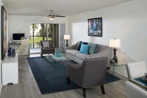 Living room and work from home area with sliding glass doors to balcony, wood-look flooring, and ceiling fan