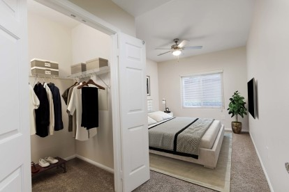 Bedroom with ceiling fan and walk in closet