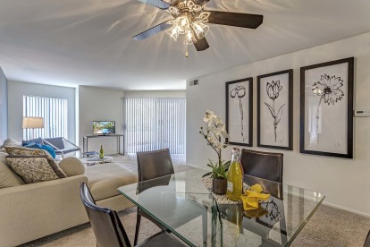 Dining and spacious living room with ceiling fan and patio